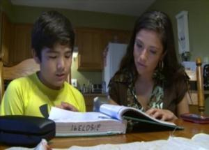 Jani Martinez helps her brother Enrique with homework. Martinez was 4 years old when her family crossed the border from Mexico into the United States.