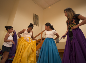 (Photo by Luis Peon-Casanova) Bianka Tovar adjusts her yellow skirt during a recent Mexican baile rehearsal, while Myah Villafranca (from left to right0, Jackie Martinez and Angelina Jurado watch.